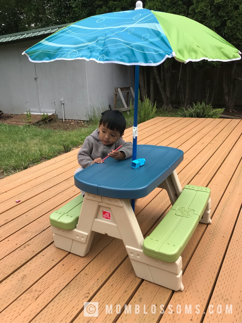 Step2 sit and play kids picnic table with umbrella mom blossoms the bench is good for 4 toddlers or a parent can sit on the other bench its plastic but sturdy he loves sitting here and playing with his toys while my watchthetrailerfo
